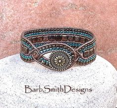 The Diamond Princess in Bronze  The Diamond Princess is a slimmer version of the Queen of Diamonds. This Princess was designed with a focal point of (2) two diamonds of Jet Bronze Picasso tile beads, each with a beautiful hint of blue, hand-stitched in a weave of Metallic Brown Indian leather cord. The bronze tiles are surrounded by (4) four rows of Transparent Lustered Teal and Metallic Iris Brown seed beads. The front closure is a 5/8 antique bronze Bali button with a beaded button loop…