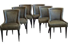 Set of six midcentury dining chairs that have been completely restored. The wood legs have been refinished in an espresso brown and have the original brass caps on the front legs. The chairs have been newly reupholstered in a distressed olive green leather and have French brass nailheads all around the back and the sides of the arms. (5899 from Maude Woods on Vintage/Mkt OKL; retails 9000)