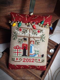 cross stitch pillow ornament with tiny Christmas lights for decoration