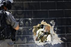 July 9, 2013. An Israeli border policeman looks at his colleague through a hole in a section of the controversial Israeli barrier in the West Bank village of Abu Dis, near Jerusalem. (Photo: Mohamad Torokman—Reuters)