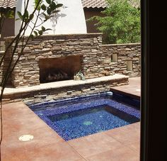 Nice cobalt blue glass tile jacuzzi with the outdoor fireplace