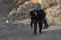 FALLEN COMRADE: A Free Syrian Army fighter carried the body of a fellow fighter who was killed amid clashes with Syrian government forces in...