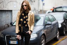 Chiara Ferragni wearing a vintage leather jacket, Moschino bear-print sweater and scarf, Black Orchid leather overalls, Céline shoes, Dita Eyewear sunglasses and Prada backpack before the Dsquared2 Fall/Winter 2015-2016 fashion show in Milan, Italy