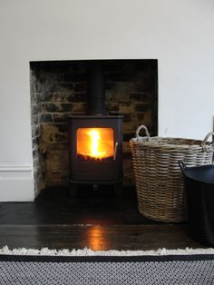 Wood burning Morso stove in the living room with basket and drug for coal and wood.