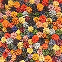松ぼっくりのアート。 いろいろなカラーに色付けされた松ぼっくりを壁掛けのアートにした作品です。 お花みたいでとってもかわいいですね♪