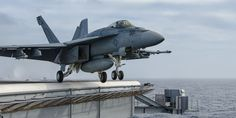 """A Boeing F/A-18E Super Hornet, from Strike Fighter Squadron 97 (VFA-97) """"Warhawks,"""" launching from the waist of the USS John C. Stennis (CVN 74)."""