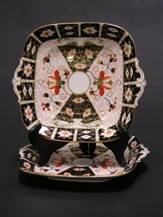 PAIR OF ROYAL CROWN DERBY DECORATED SQUARE CAKE PLATES, dated 1924 and 1927, Imari pattern, #2451, with two scroll detailed handles; 10-1/2 inch length