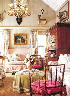 This is one of my all time favorite living rooms.  So glad to find this pic to pin!  I have saved my magazine issue that featured this some years back.  Love the antlers, the florals, beadboard walls, Bamboo chairs, highboy. I love every single thing in this room.