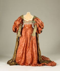 """Renaissance or """"Juliet"""" fancy dress costume, 1928-29. Made of silk brocade, metallic brocade, and plastic (trim). This theatrical, Renaissance-style costume in salmon brocade is often referred to as Marjorie Merriweather Post's """"Juliet"""" costume. Post wore this costume to the Everglades Ball on March 7, 1929. The Everglades Ball was a fancy dress ball held annually at the Everglades Club in Palm Beach, Florida. Hillcrest Estate Museum."""