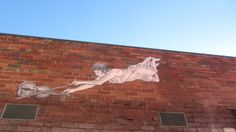 Violinist graffiti. Woman floating on a wall with a violin.