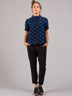 <p>Short sleeved top with a short funnel neck made from black brocade decorated with royal blue polka dots. This top has a definite 50's feel due to the swingy boxy, slightly a-line cut and the pattern. There are darts at the neck and an exposed zipper at the center back at the neck. Fully lined. 35% wool, 35% acrylic, 18% polyester, 12% nylon.</p>