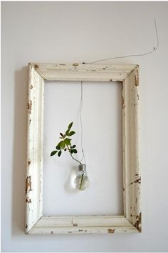 - empty frame with suspended lightbulbvase plus leaves - Orietta Marcon of Vicenze-based design studio Civico Quattro in a loft in italy.