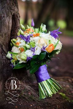 Purples and Oranges blended together for a stunning bridal bouquet.  Featuring lisianthus, white and blush roses, clematis and tulips