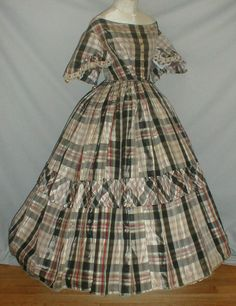 "Plaid silk ball gown; white & black trim on sleeves attached with black silk trim with silk balls; piping at neck, armscyes & waist; bodice lined with cotton; back hook & eye closure; skirt fully lined with cotton; bust: 31""; waist: 24""; skirt length: 37""; hem width: 140"""