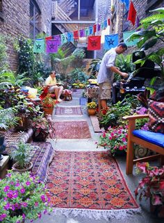 Colorful outdoor patio with prayer flags, old rugs, and tons of potted flowers and greenery