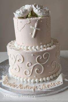 Modern Day Religious #21Religious This cake design is iced in a very light tint of grey with accents of white buttercream swirls and polka dots to really make this cake fresh and modern. The gum paste flowers and a piped on rosary are added to make a perfect topper