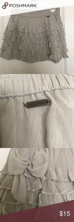 Hollister Beautiful ruffle mini skirt This mini skirt is very cute and feminineD color is a light grey that can be combined with almost any other color. Material is polyester. Worn a couple of times. In perfect condition Hollister Skirts Mini