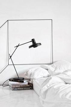 White bedroom white bedding, black lamp, geometric sculptural wall art