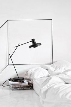 White bedroom white bedding, black lamp, geometric sculptural wall art