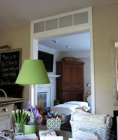 How to Make a Fake Transom for a Doorway - all you need is molding and a discount store door mirror to transform the blank space above a door!