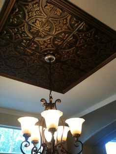 Tin ceiling...galvanized tin squares, two different color layers of paint, and painted wood trim in the shape of a frame