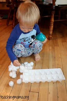 Sorting cotton balls into ice cube trays. Fun winter project for the little ones, turn it into a snowman set-up!