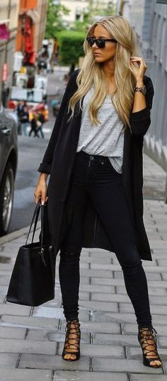 Street fashion grey shirt, long black coat and strapped heels
