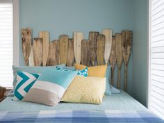 New and vintage paddles are stood up to create this swimmingly fantastic headboard. See more photos of this beach-side bedroom.