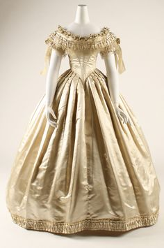 Wedding dress of ecru silk satin (1856-59)  Wide, shallow neckline extends from shoulder to shoulder.  The decolletage is elaborately pleated & ornaments.  The bodice is tightly cinched & fitted.  The skirt is a full bell over a crinoline hoop.   (Front view)