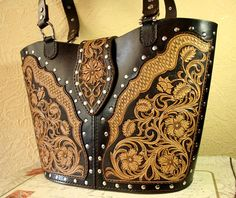 Gorgeous hand-tooled leather tote bag with rich sheridan style design in noble brown colors. High-quality vegerable tanned leather. Original design. Lining - genuine suede milld blue color. A roomy zip pocket inside. Large flat pocket on the back side of the bag . Beautiful and comfortable strap closure with a hidden snap. Comfortable straps ornamented with silver color rivets. Dimensions: Height - 25 cm (10 inches) Width - 36 cm (14 inches)