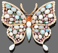 A gem-set butterfly brooch The body and wings set throughout with cabochon opals, interspersed with circular-cut pink sapphires and tsavorites, within an openwork surround set with brilliant-cut diamonds, diamonds approx. 1.85ct. total, width 6.2cm.