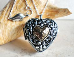Music box locket,  heart shaped locket with music box inside, in silver tone with heart on front cover.