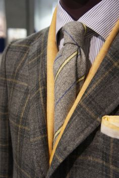 Color coordination and eye for detail (down to the matching bands of yellow, with the scarf) are superb. May want to try a different kind of tie, however, just for texture variation. Still looks very nice.
