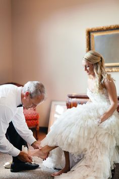 Father putting the brides shoe on ....awww :)  Cute pic.  Mom putting veil on, Father putting shoes on never heard of but sweet.  Love the way bride is leaning towards Dad.  Definite ....aww moment.