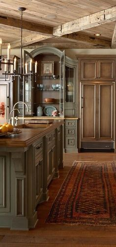I love the beams, the Persian rug, the painted arched armoire.  What a beautiful kitchen.