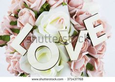 Table arrangement with roses, wedding rings and love sign