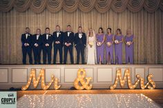 The bridal party onstage at The Heritage with the glowing Mr & Mrs light up letters. Weddings in The Heritage Hotel, by Couple Photography.