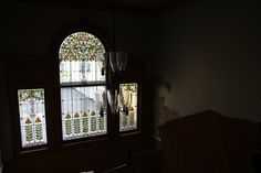 Large arched art deco design stained glass windows overlooking main staircase.