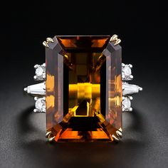 An enchanting golden amber colored emerald-cut Madiera Citrine glistens in this wonderful 18 karat gold mount. The Citrine is elegantly presented with a slight variation of a traditional style cocktail ring with a tapered baguette and two round brilliant-cut diamonds enlivening each shoulder