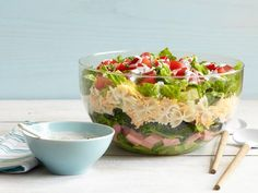 This summer 7-Layer Pasta Salad has it all: layers of creamy avocado, heaping spoonfuls of diced ham, crunchy broccoli, hearty pasta, cheddar cheese and a topping of crispy romaine.