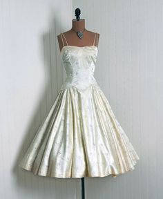 ETA: Found the sellers website; TimelessVixen.com. Unfortunately this Etsy listing is gone. I love this!   1950's Vintage Ivory-White Embroidered Metallic-Silver Shimmer Silk-Satin Couture Duel-Strap Sweetheart Low-Cut Plunge Nipped-Waist Rockabilly Ballerina-Cupcake Princess Full Circle-Skirt Swing Bombshell Garden Wedding Formal Cocktail Party Dress
