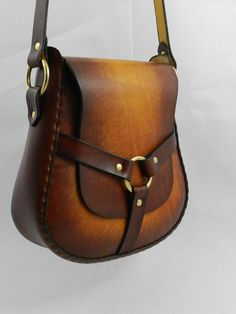 This bag is made of 8 oz. special-tanned yellow latigo which allows for the beautiful yellow and brown earth tones. The ring and 3 strap closure make securing this bag simple by sliding the flap under it. The hand-stitching gives this bag pleasing shape and contours and the cut-out on the front panel allows for easy access. This bag can be carried cross-body or over the shoulder. The strap will be sized according to length designated when ordering. It features solid brass hardware…
