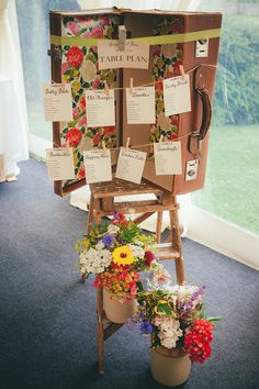 Vintage suitcase table plan balanced on an antique step ladder & decorated with jugs of wild flowers - Lucy G Photography - A marquee wedding with a lace gown and colour pop theme with mix and match centrepieces.