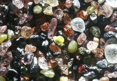 The glacially deposited sands around Lake Winnibigoshish, Minnesota, contain abundant sediments from the igneous and metamorphic minerals of the Lake Superior basin. A sample includes pink garnets, green epidote, iron-rich red agates, black magnetite, and hematite. Image Copyright © 2008 Dr. Gary Greenberg.