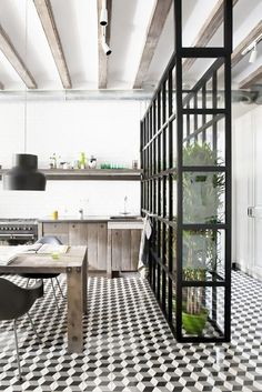 Minimalist kitchen with exposed ceiling beams, graphic tiles floors, and a wall of greenery