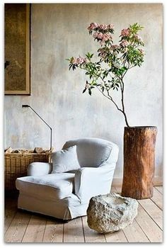 family room, grandma's chair Indoor flowering tree branch + white slipcovered accent chair + neutral and wabi sabi