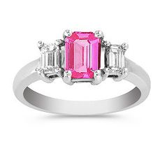 Shane Co. 1 1/4 ct. t.w. Emerald Cut Pink Sapphire and Diamond Three-Stone Ring.This emerald-cut center pink sapphire, at approximately .84 carat, was hand-selected for its exceptional color and beauty. Two emerald-cut accent diamonds, at approximately .43 carat TW add sparkle and shine. The stones are set in an elegant 14 karat white gold setting of the highest quality. This unique three-stone ring has an approximate total gem weight of 1.27 carats.