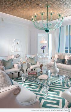 Decoração clássica em branco e turquesa na sala de estar. O sofá branco, o lustre, a mesa de vidro e o tapete azul turquesa garantiram elegância ao ambiente.