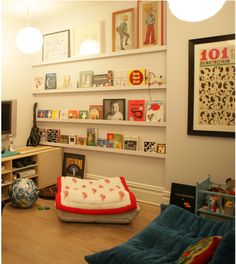 Interior decorator Jan Eleni Lemonedes converted a playroom wall into a display area for books, photos, toys, and more. By adding narrow shelves to the length Kids Storage, Wall Storage, Storage Ideas, Big Floor Pillows, Bookshelves Kids, Bookshelf Ideas, Book Shelves, Kids Corner, Kid Spaces