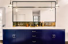 Contemporary bathroom boasts a single cobalt blue vanity divided into his and her sections topped with white marble framing his and her sinks under an Ann Sacks Pyrite Square Tile backsplash and steel framed vanity mirror illuminated by Small Gale Hanging Pendants suspended from the ceiling.